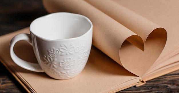 Cuore fatto da fogli di libri con una tazza su un tavolo di legno