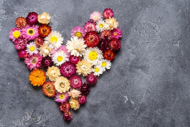 Cuore fatto dai fiori su fondo grigio