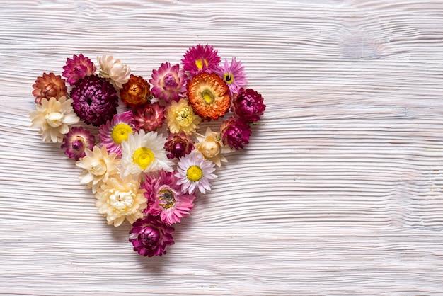 Cuore fatto dai fiori su fondo di legno