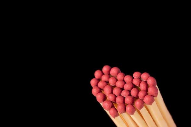 Cuore fatto di fiammiferi con testa rosa isolato sul nero