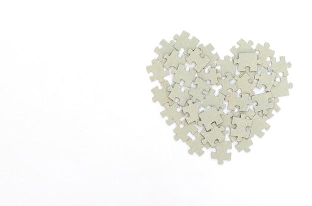 Cuore fatto di puzzle su bianco.