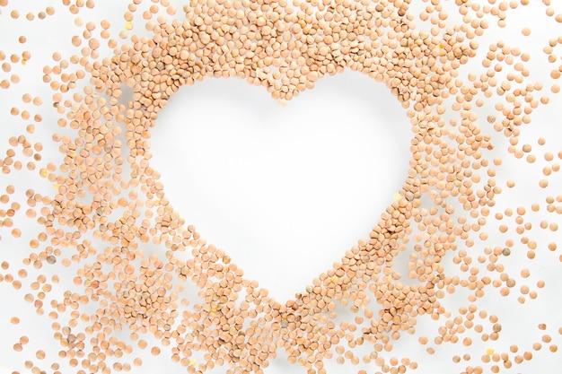 Cuore fatto di lenticchie crude sul muro bianco, vita sana e concetto di nutrizione