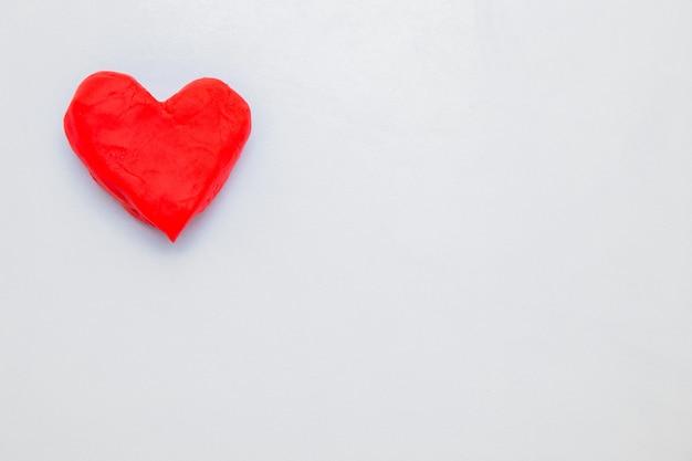 A lato della foto c'è un cuore di pasta rossa da modellare