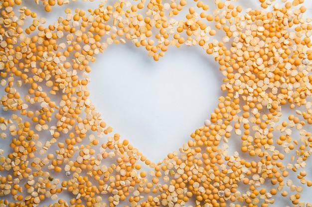 Cuore fatto di piselli spezzati sul muro bianco, vita sana e concetto di nutrizione