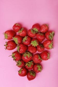 Cuore di fragole su uno sfondo rosa