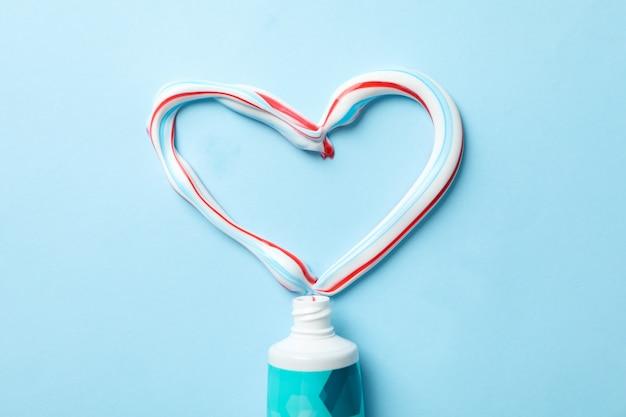 Cuore fatto di dentifricio e tubo sulla superficie blu