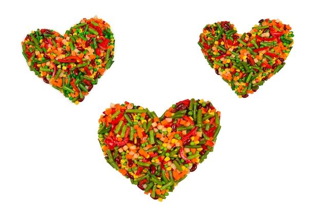 Cuore fatto di verdure. mais, carota, peperone, fagiolini. isolato su bianco.