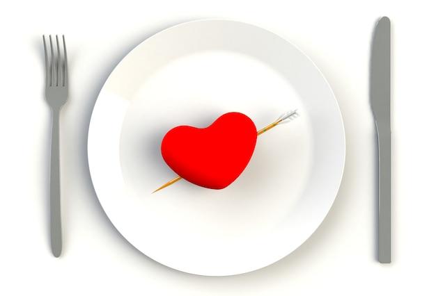 Cuore su piastra, coltello e forchetta