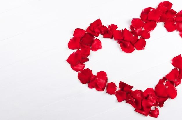 Cuore di petali di rose rosse sulla tavola di legno bianca. copia spazio