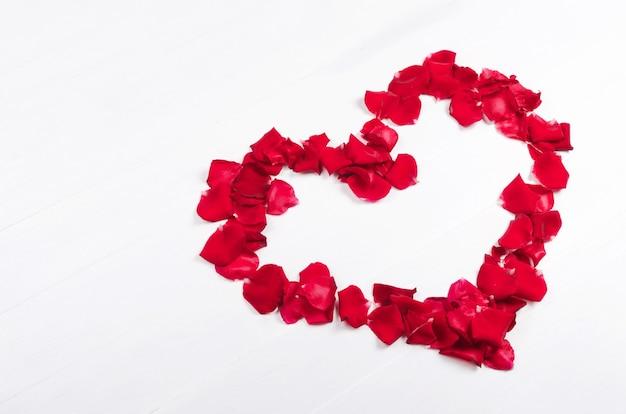 Cuore di petali di rose rosse sulla tavola di legno bianca