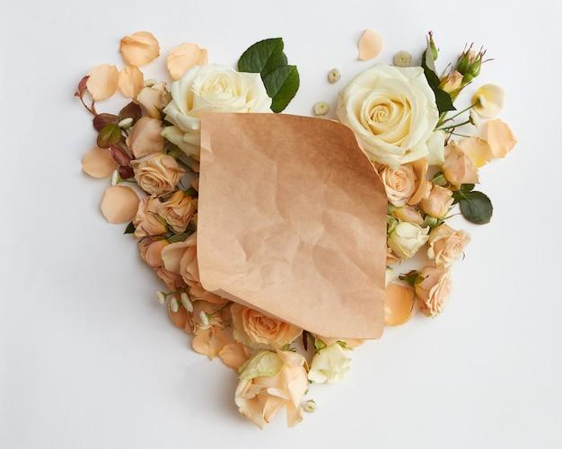 Cuore di rose fiore e un pezzo di carta, laici piatta