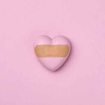 Cuore sigillato con cerotto medico su sfondo rosa. il concetto di malattia cardiaca o dolore o delusione e trattamento e recupero del sudore. colore trendy di tendenza e idea minimale.