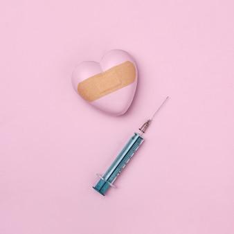 Cuore sigillato con cerotto medico e una siringa per vaccinazione o iniezione. l'idea di una malattia cardiaca o di una guarigione dalla tristezza o dalla delusione. concetto di tendenza moderno minimale.