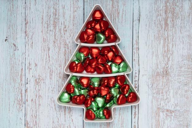 Caramelle al cioccolato a forma di cuore su un piatto a forma di pino con colori natalizi rossi e verdi