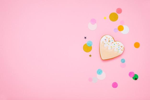 Biscotto a forma di cuore su sfondo rosa con uno spazio vuoto per il testo. vista dall'alto, piatto.