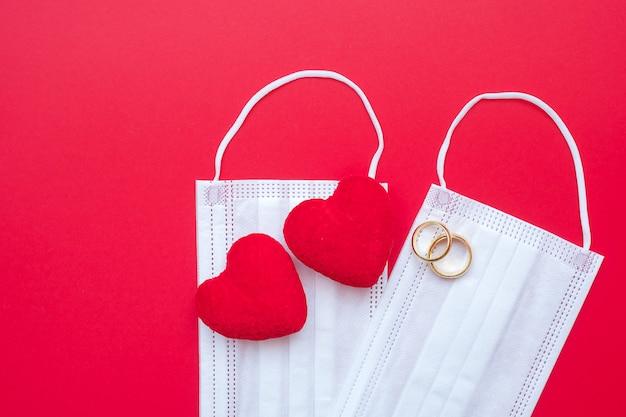 Decorazione a forma di cuore, anello di fidanzamento dorato e maschera medica su sfondo rosso contro l'infezione da malattia da coronavirus.