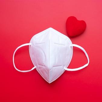 Decorazione a forma di cuore e maschera medica n95 su sfondo rosso contro l'infezione da malattia da coronavirus