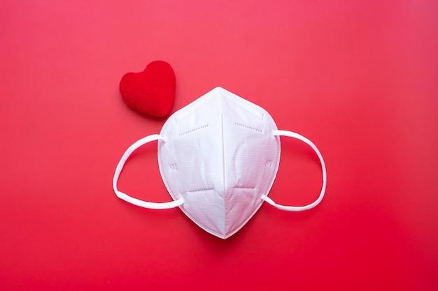 Decorazione a forma di cuore e maschera medica n95 su sfondo rosso contro l'infezione da coronavirus.