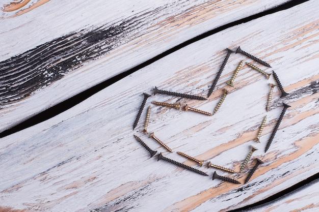 A forma di cuore da strumenti di costruzione su fondo in legno