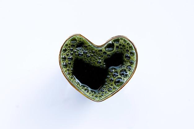 Il bicchiere a forma di cuore di centella asiatica lascia il succo per la salute su bianco. copia spazio