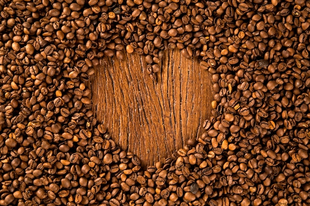 Forma di cuore realizzata con chicchi di caffè sulla tavola di legno