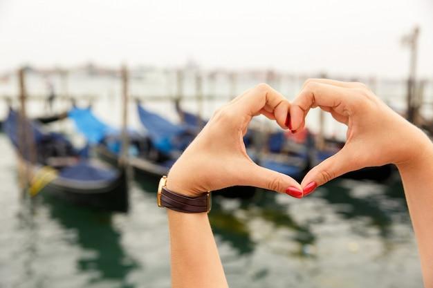 A forma di cuore realizzato con le mani con splendida vista sulle gondole