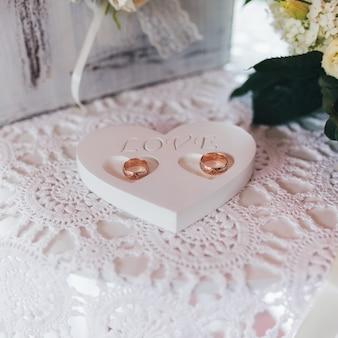Oggetto a forma di cuore con parola d'amore e fedi nuziali su tovagliolo cucito rustico