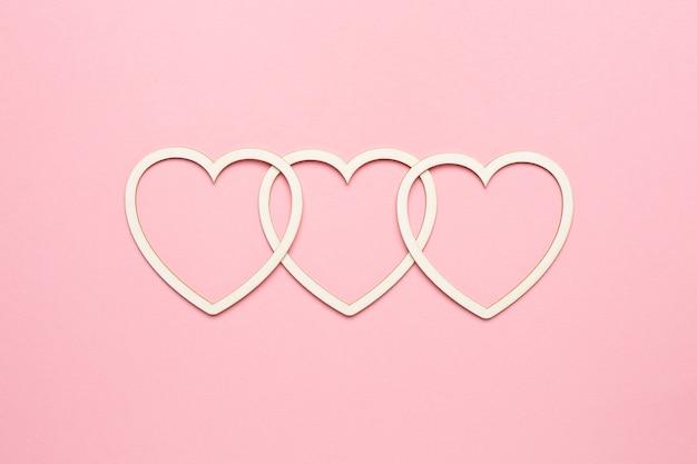 Forma di cuore su sfondo rosa pastello. carta di san valentino di concetto. vista dall'alto, copia spazio per il testo