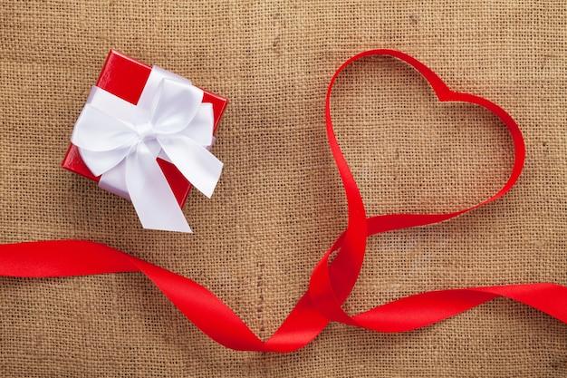 Nastro a forma di cuore e confezione regalo su sfondo di tela di san valentino con spazio di copia