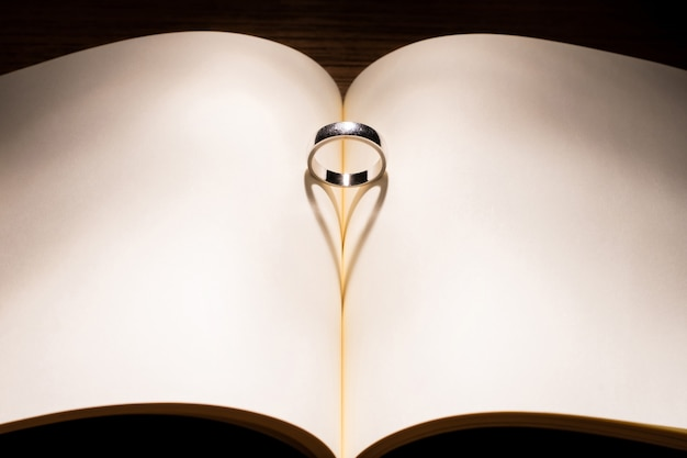 Ombra a forma di cuore con l'anello al centro del libro vuoto san valentino e ogni giorno del concetto d'amore