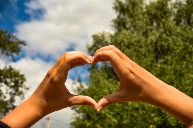 Segno universale a forma di cuore per amore e romanticismo. mani femminili a forma di cuore