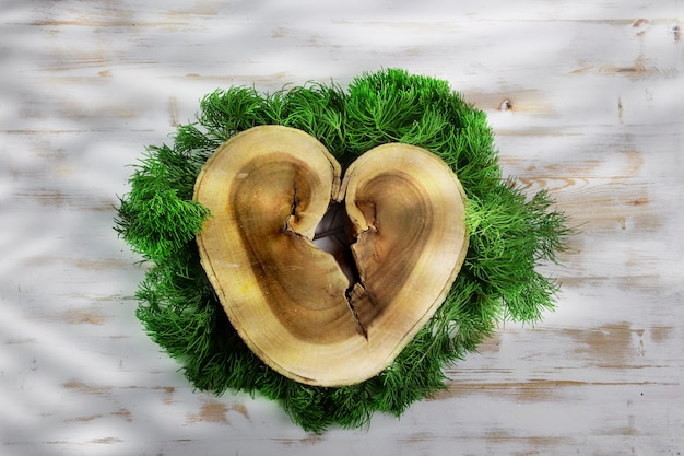 Fetta di registro in legno a forma di cuore su foglie di pino