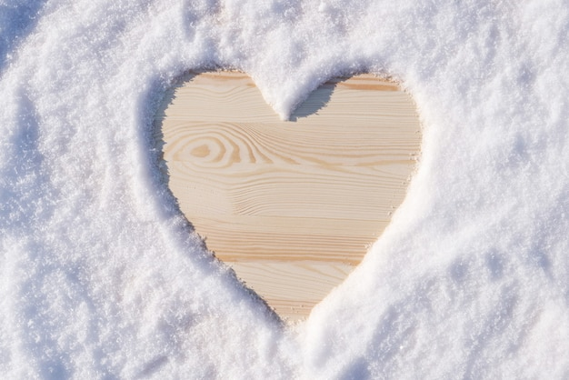 A forma di cuore sul tavolo di legno fatto di neve