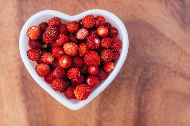 Ciotola a forma di cuore piena di fragole selvatiche succose rosse mature su fondo di legno. vista dall'alto, copia spazio