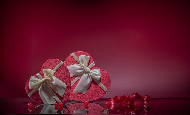 Regali per gli amanti della scatola a forma di cuore sullo sfondo rosso della superficie dello specchio