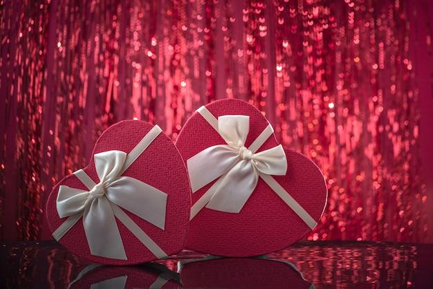 Regali per gli amanti della scatola a forma di cuore sulla superficie dello specchio rosso brillante sfondo bokeh