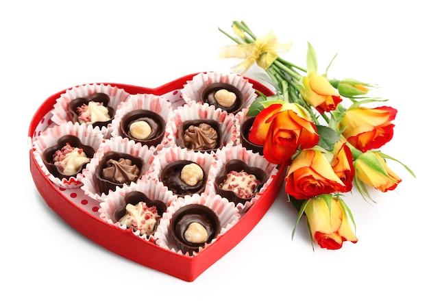 Scatola a forma di cuore con caramelle e fiori, isolato su bianco