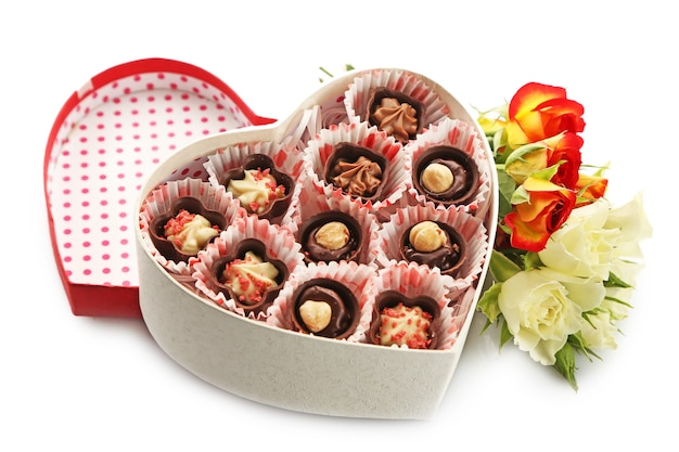 Scatola a forma di cuore con caramelle e fiori isolati