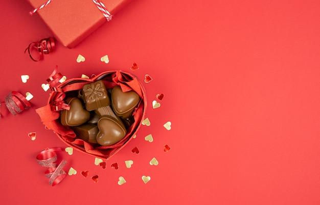 Scatola con cioccolatini su fondo rosso a forma di cuore. giorno di san valentino
