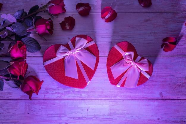 Scatole a forma di cuore amano i regali su superfici in legno petali di rose luce dura viola neon