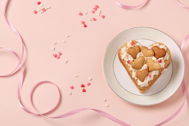 Torta a forma di cuore su sfondo rosa per il giorno di san valentino