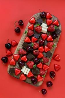 Caramelle a forma di cuore, cioccolato fondente e bianco, fragole e bacche di ciliegie dolci su tagliere di salumi su sfondo rosso. primo piano, vista dall'alto.