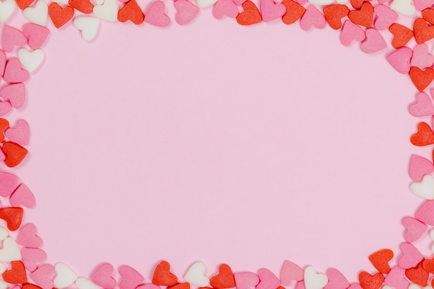 Caramelle a forma di cuore sparse sul concetto di matrimonio di amore sfondo rosa