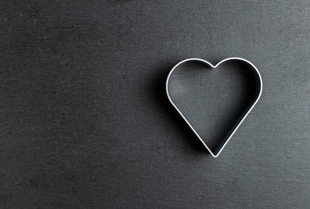 Tagliabiscotti a forma di cuore su ardesia