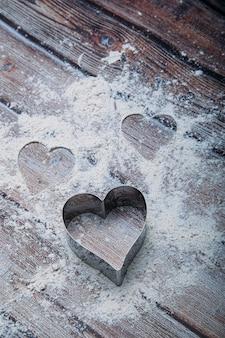 Tagliabiscotti a forma di cuore sul tavolo della cucina e farina.