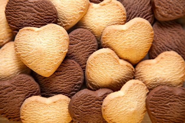 Sfondo di biscotti a forma di cuore. burro al forno e biscotti al cioccolato texture di sfondo.