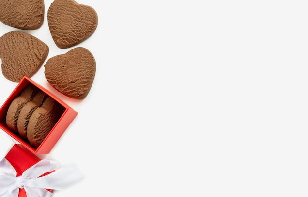 Biscotti a forma di cuore in una confezione regalo su sfondo bianco. spazio di copia dall'alto verso il basso