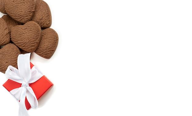 Biscotti a forma di cuore e una confezione regalo rossa con un fiocco bianco su sfondo bianco. sfondo festivo