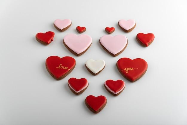 Biscotti a forma di cuore con glassa di zucchero colorata. sfondo bianco. san valentino.