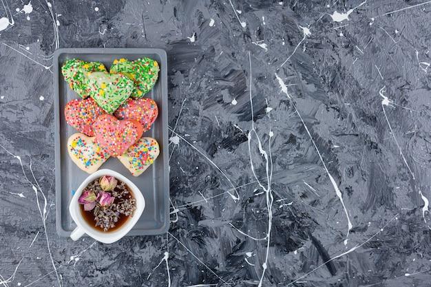 Biscotti a forma di cuore con granelli colorati e una tazza di tè nero.